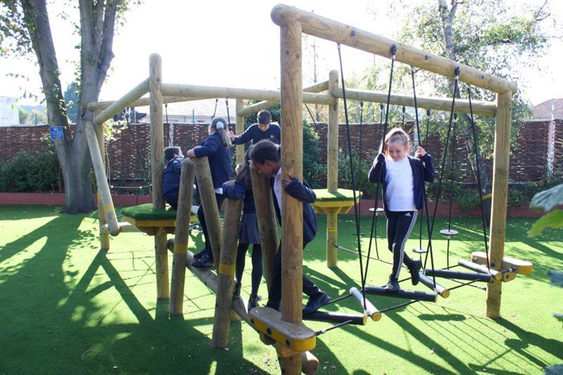 Children traversing through a school playground climbing frame