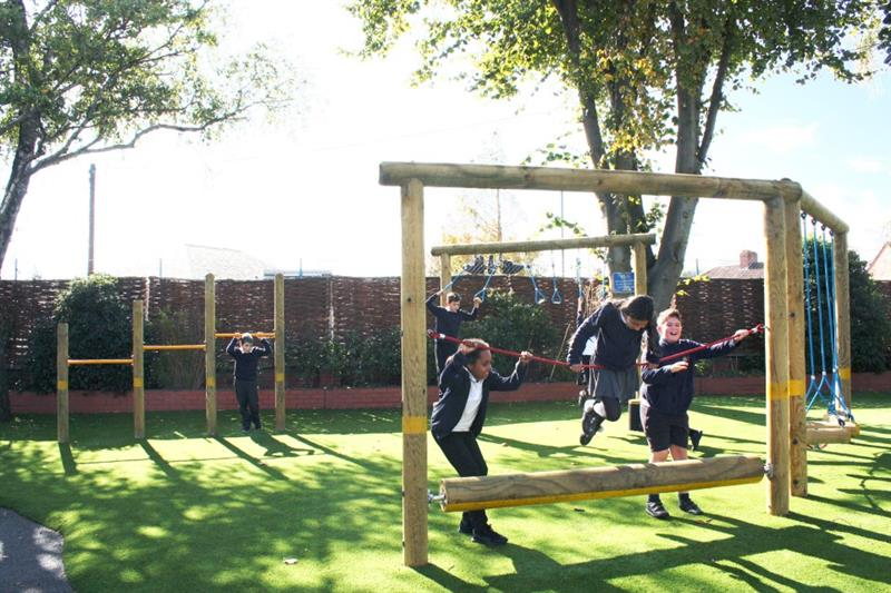 Children swinging and climbing on a playground trim trail