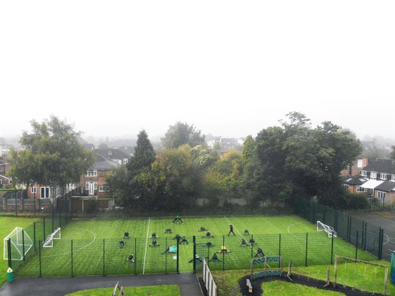 A primary school PE lesson taking place on a muga
