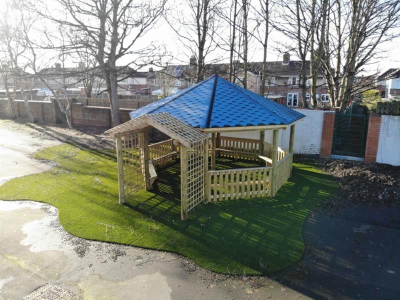 A 6m outdoor gazebo with a blue roof and fenced sides installed into a school playground with artificial grass underneath it