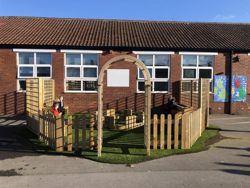 3 children sat on planter benches surrounded by bow top timber fencing and trellis fence panels to create a quiet space