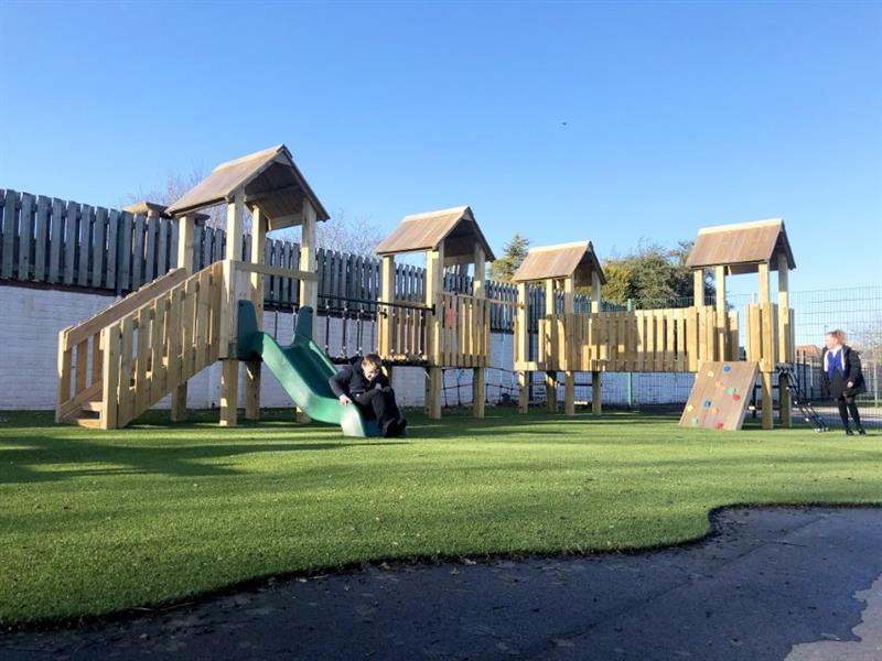 Pentagon Play's Goodrich Modular Play Tower featuring 4 decks, climbing ramps, climbing nets, stairs and slides installed on a school playground with artificial grass underneath