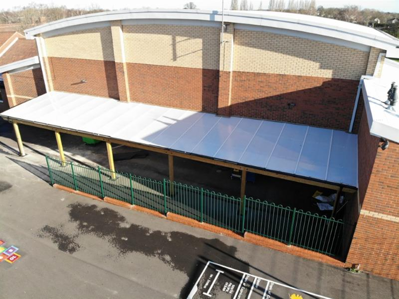 18m x 4m canopy installed against the school building to provide shade and shelter to parents and children