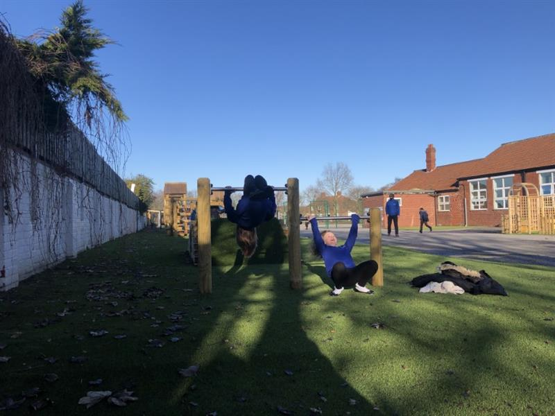 two children rolling over a set of roll over bars in blue school jumpers with coats placed to one side