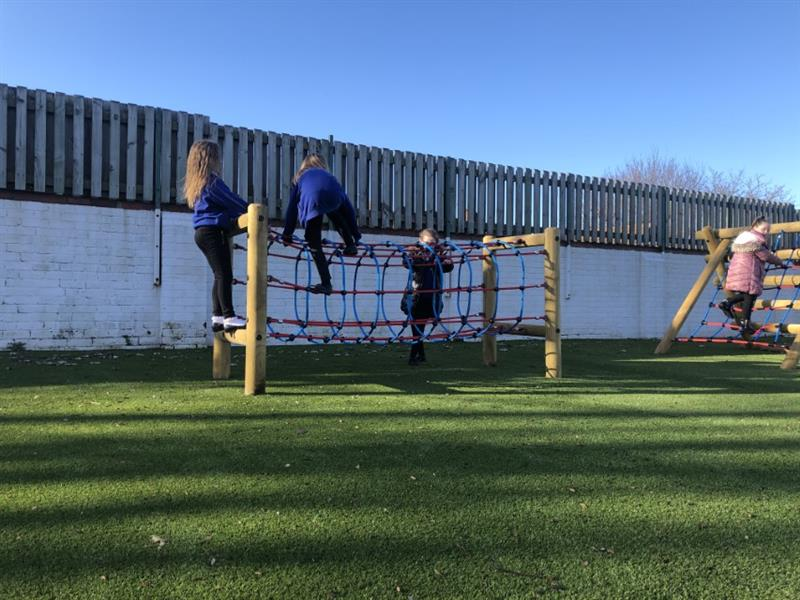 3 children climbing on top of a rope tunnel with bright blue and red ropes