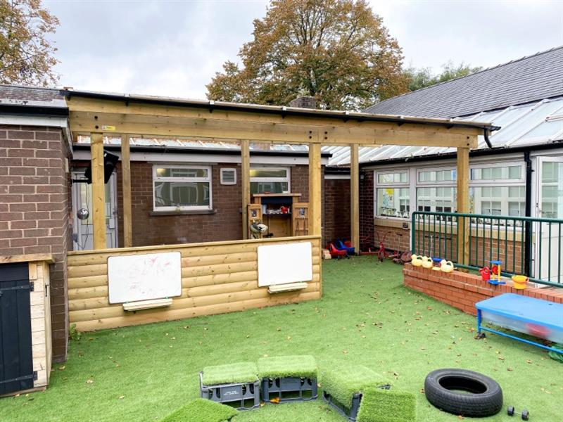 A timber canopy installed adjacent to the nursery classroom doors