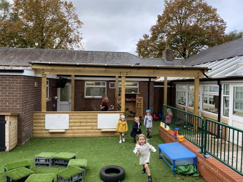 Nursery children playing underneath a timber canopy