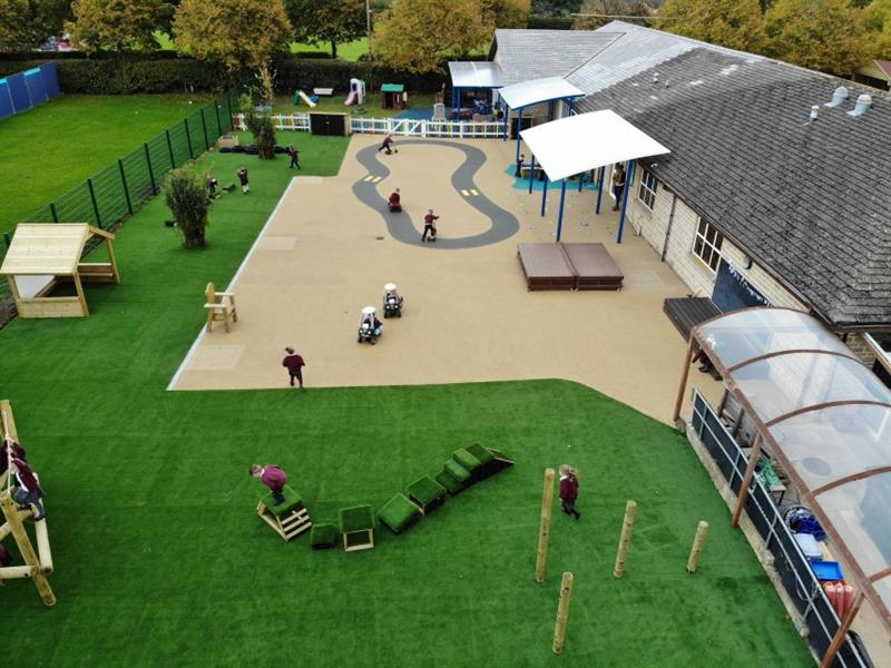 Aerial view of 14 children playing on different areas of the playground with one child stood on a get set go block and one teacher stood underneath a canopy.