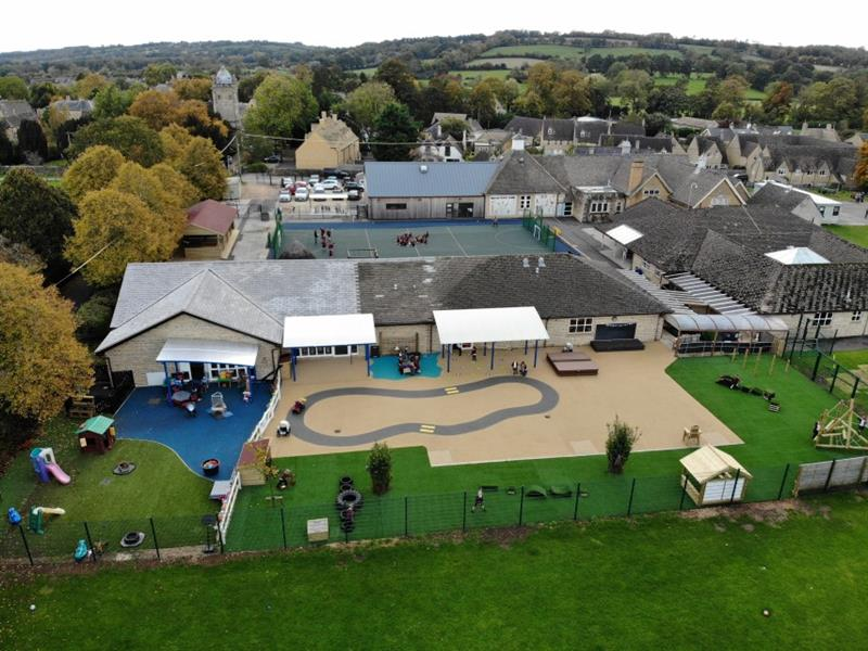 Aerial view of the whole school including playground transformation with wet pour surfacing, artificial grass, get set go blocks, giant play house and climbing frame with children playing in the football pen behind the school.