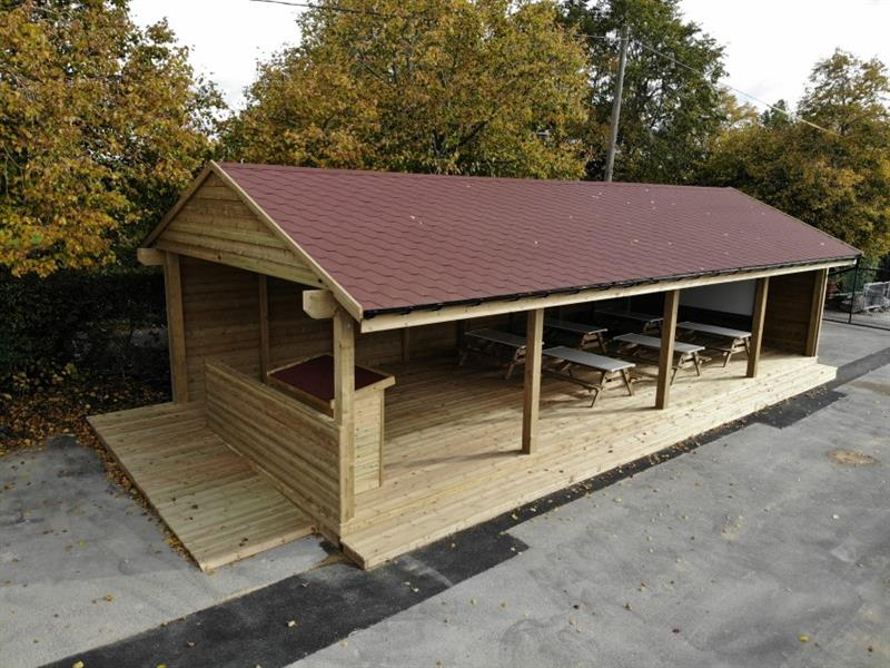 Huge outdoor timber classroom with 6 desk benches underneath, a table for a teacher to stand at and a whiteboard on the other side of the classroom.