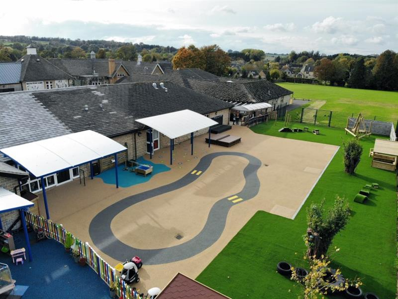 High image of wet pour surfacing and roadway which has been installed beside artificial grass. Surfacing is next to the school building with two small canopies, a messy play area, and a performance stage.