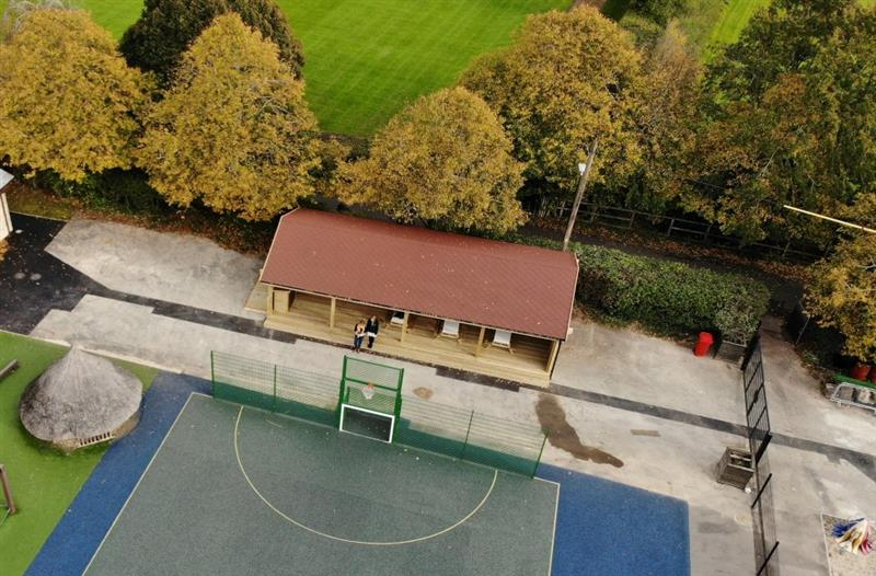 Aerial view of the huge outdoor classroom with two teachers stood outside which has been installed next to football pen and large trees behind the classroom.