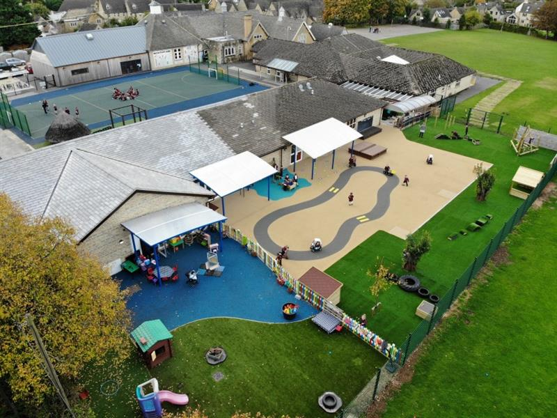 10 children playing on the wet pour surfacing with a roadway which has been installed next to the messy play area with one teacher wearing a grey jumper stood on the artificial grass.