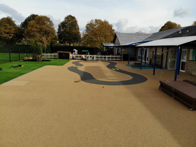 Wetpour rubber safety surfacing with a roadway installed with 2 yellow zebra crossings, the school building is on one side and artificial grass has been installed onto the other side.