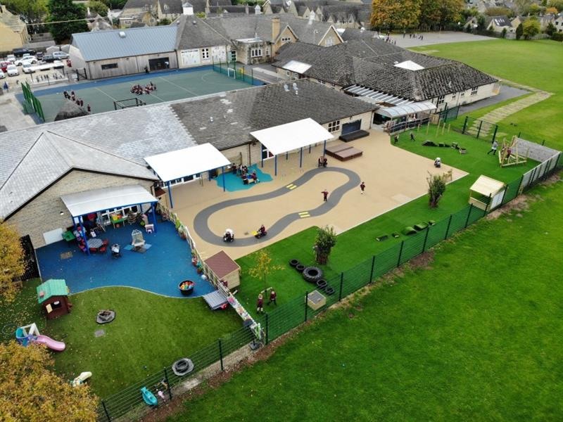 Aerial view of school playground development showing the artificial grass, playground surfacing with a roadway, performance stage, climbing frame, and the school building.