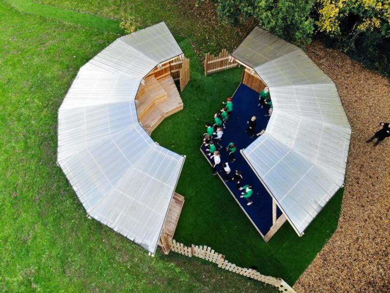 Photo taken from above the amphitheatre showing the open-circle roof with children performing on stage, amphitheatre is surrounded by grass on one side and stones on the other side.