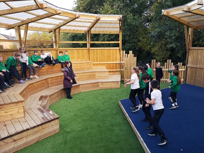 9 children performing on the performance stage in the amphitheatre which was been layered with dark blue safe turf whilst more children and one teacher watch in the audience.