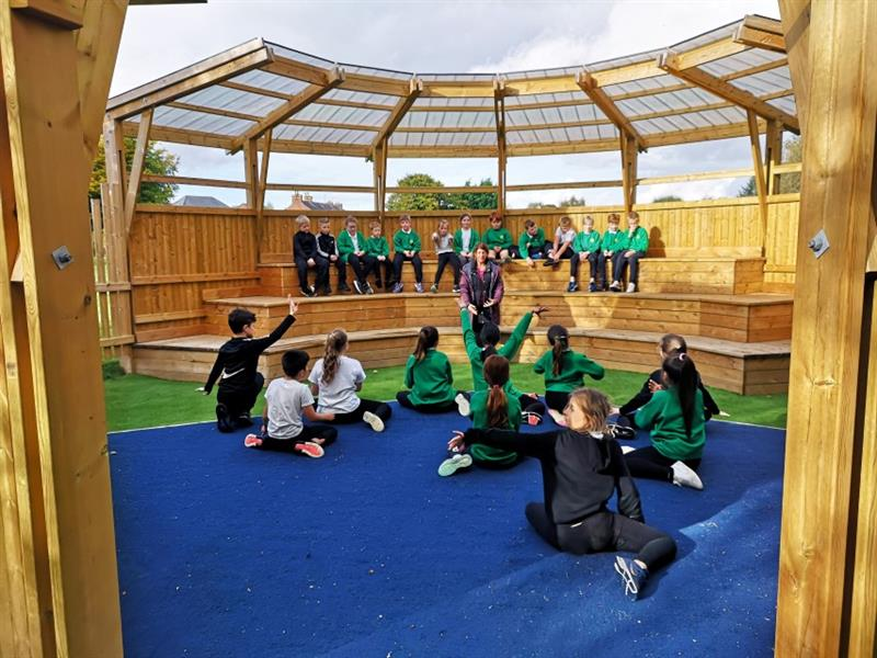 10 children sat on the blue safe turf on the stage in the amphitheatre listening to instructions from one teacher whilst 13 children sit in the audience and watch.