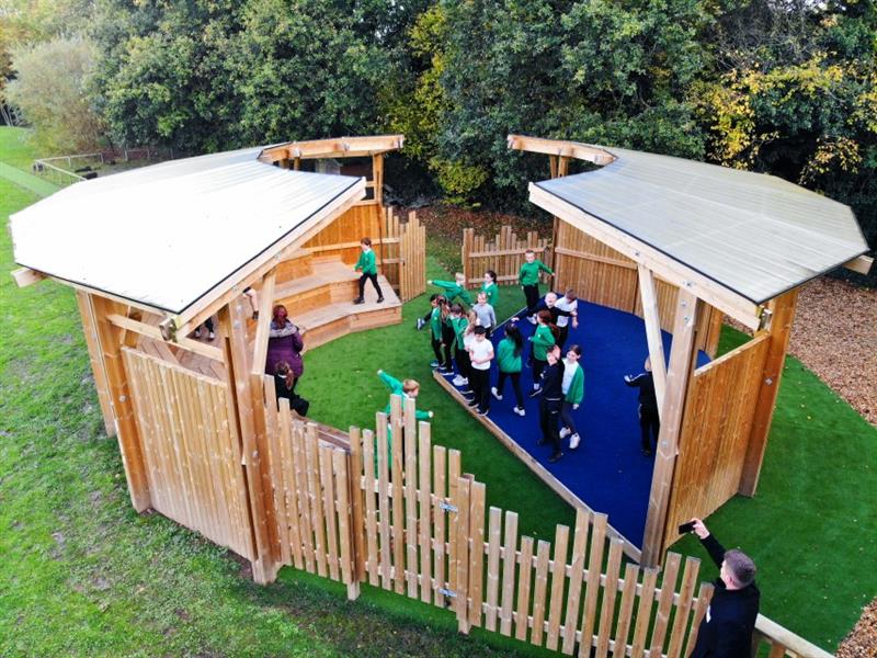 A class of primary school children performing on the performance stage in a huge amphitheatre which has been installed onto green safe turf.