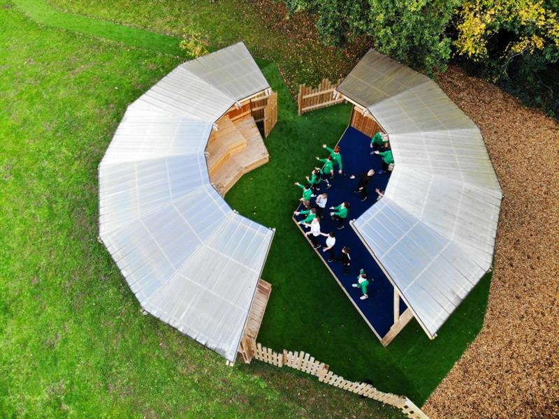 Aerial view of the amphitheatre with an open circle roof with a polycarbonate curved roof design. Children wearing green jumpers and white tops perform on the stage.