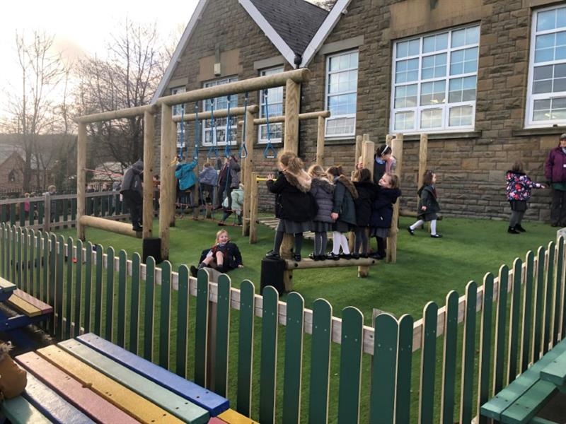 Children playing on a trim trail in a school playground