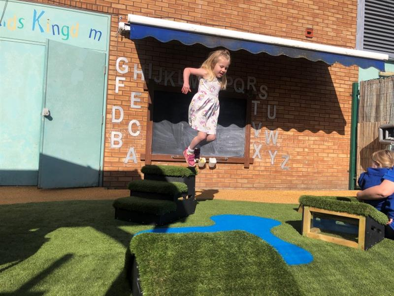 1 girl wearing a pink dress and pink shoes is jumping off a get set, go! block onto the artificial grass which has been installed in front of the school building.