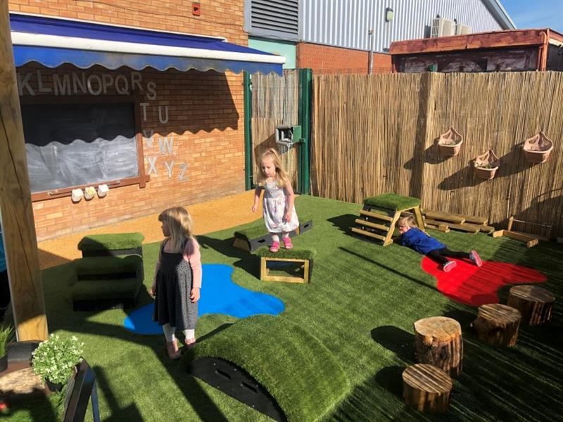 3 children playing in the new playground, one girl is lying on the artificial grass, one girl is stood on a moveable block and another girl is stood in front of a moveable block ready to start playing.