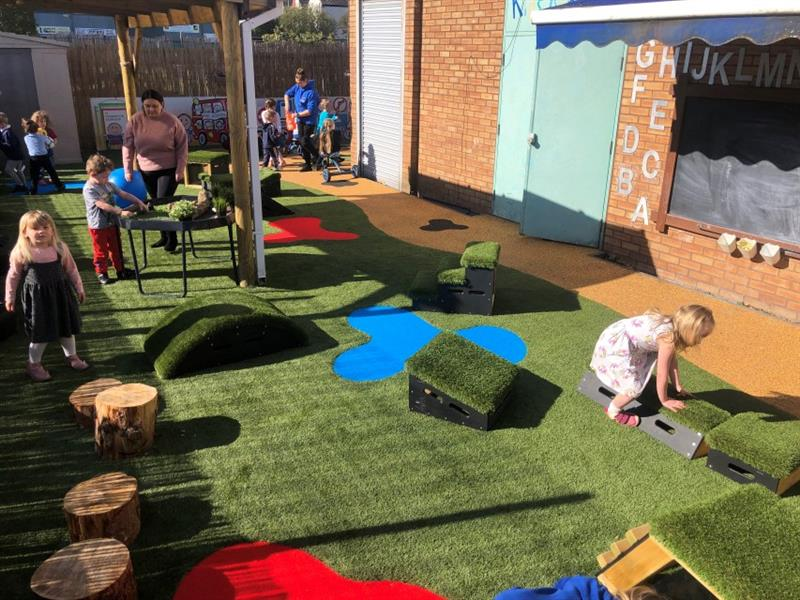 10 children playing in the playground which has artificial grass, red and blue splashes made out of safeturf and a roadway made from wetpour whilst 2 teachers supervise.
