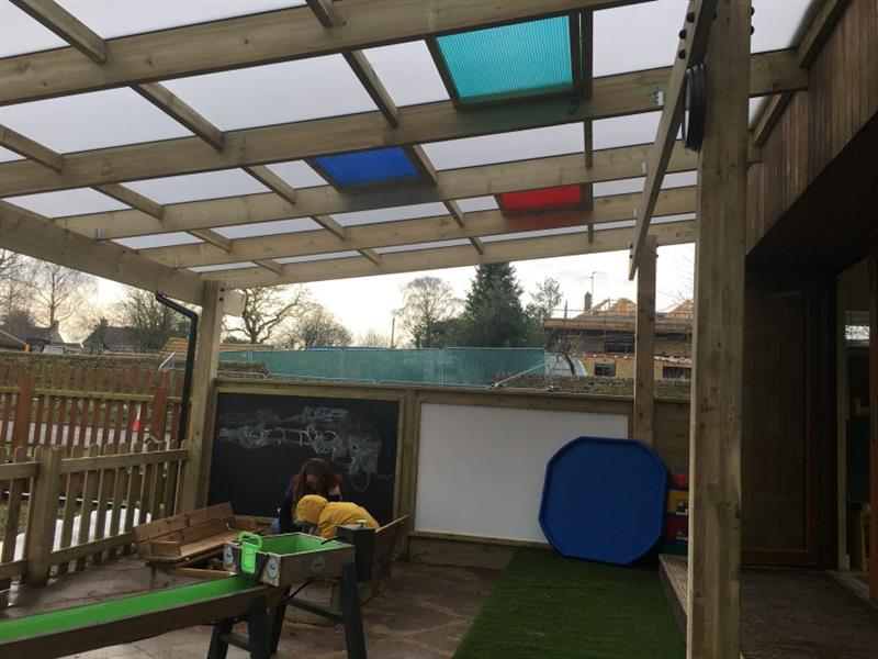 Timber canopy with a sensory roof including different coloured tiles. A child and teacher playing underneath the canopy in front of a blackboard and whiteboard.