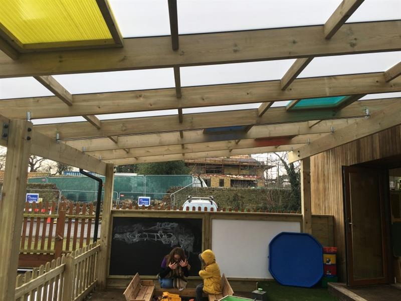 One child and a teacher playing in a sandpit in front of a black board and white board underneath the timber canopy's sensory roof.