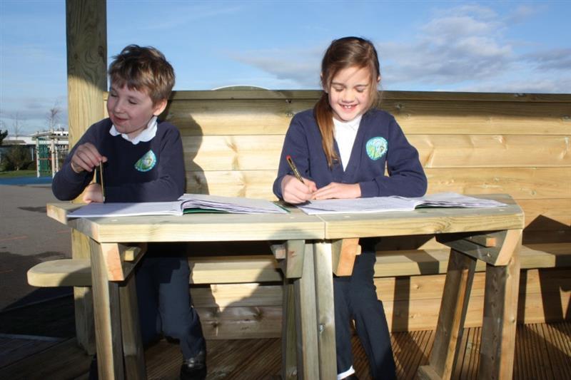 Children writing in workbooks in an outdoor classroom