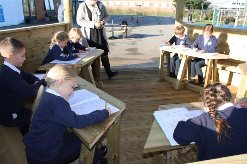 Children writing in books on outdoor gazebo workstations