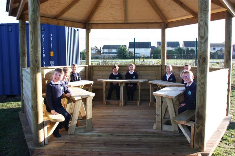 Children sitting in an outdoor gazebo