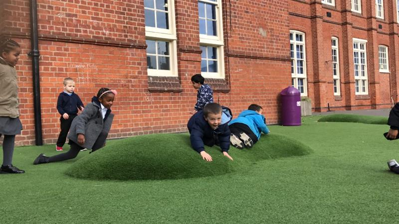 2 children lying on a surface mound that has been covered in artificial grass whilst 5 children play around the mound in front of the school building.