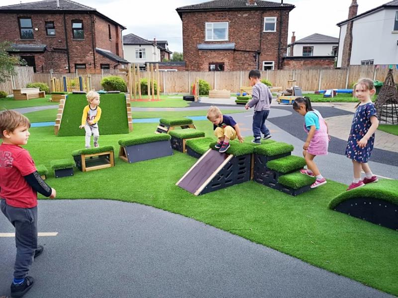 6 eyfs children are playing on the moveable get, set go! blocks that have been placed onto artificial grass in the middle of a play roadway. One child is sliding down the slide and another child wearing a pink dress is walking up the stairs.