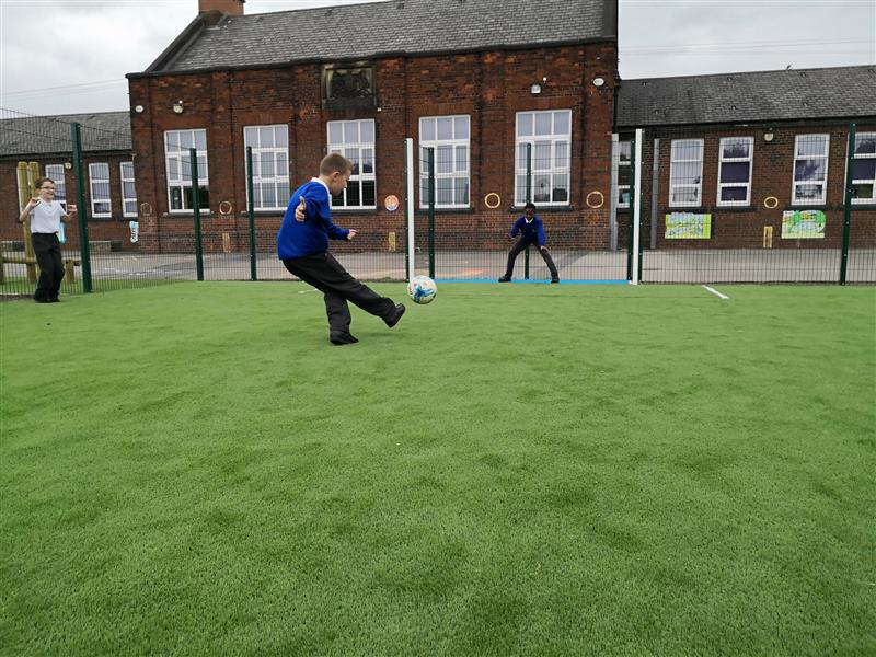 Child scoring a goal on a muga pitch