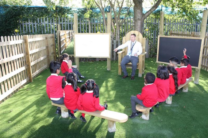 Teacher asking a class a question whilst teaching in a storytelling circle