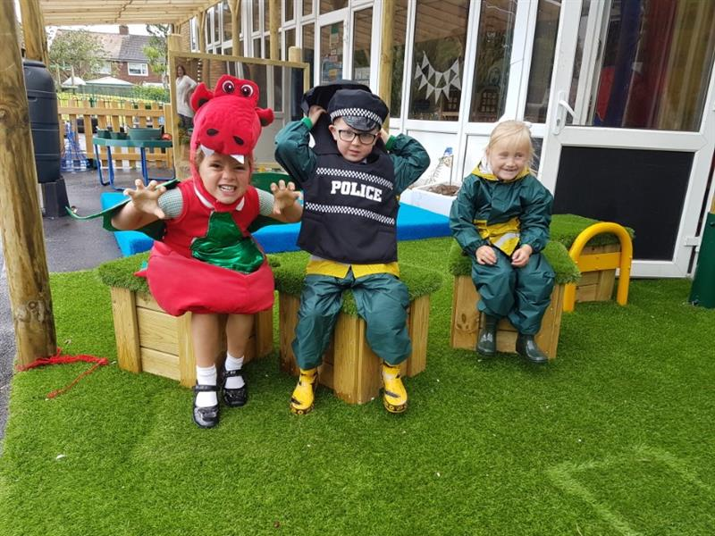 3 children sat on artificial grass topped seats, one wearing a red dinosaur costume, one wearing a policeman costume and one wearing a green and yellow waterproof bodysuit.