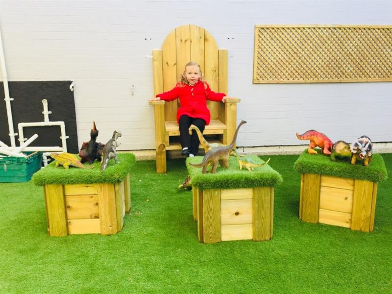 one girl sat on a storytelling chair sticking her tongue out, in front of a white brick wall with artificial grass topped seats in front of the storytelling chair that have 9 dinosaurs sat on top.