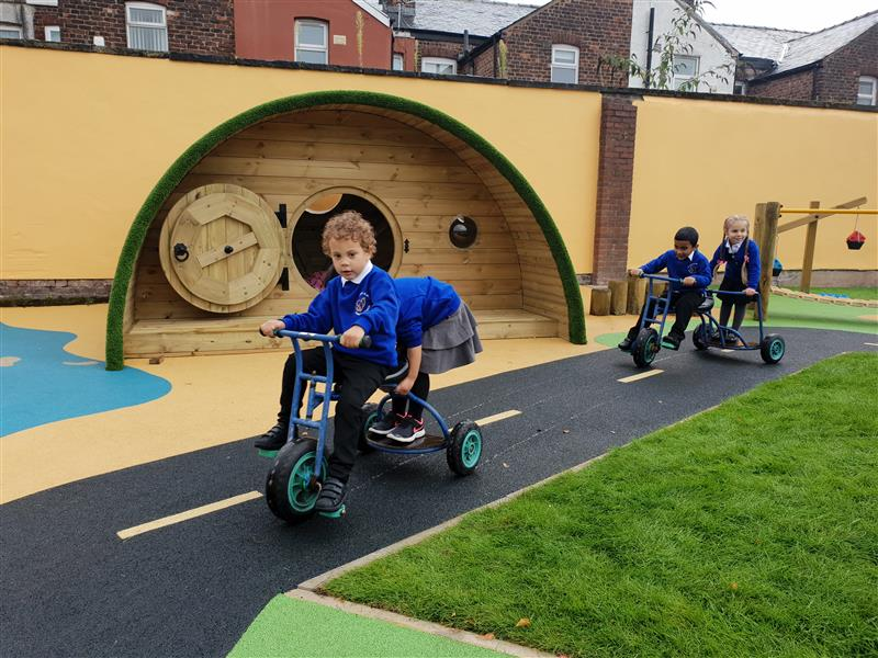4 children wearing blue school jumpers are riding on blue trikes driving around on the roadway. They are driving past a hobbit house and wobbly bridge.