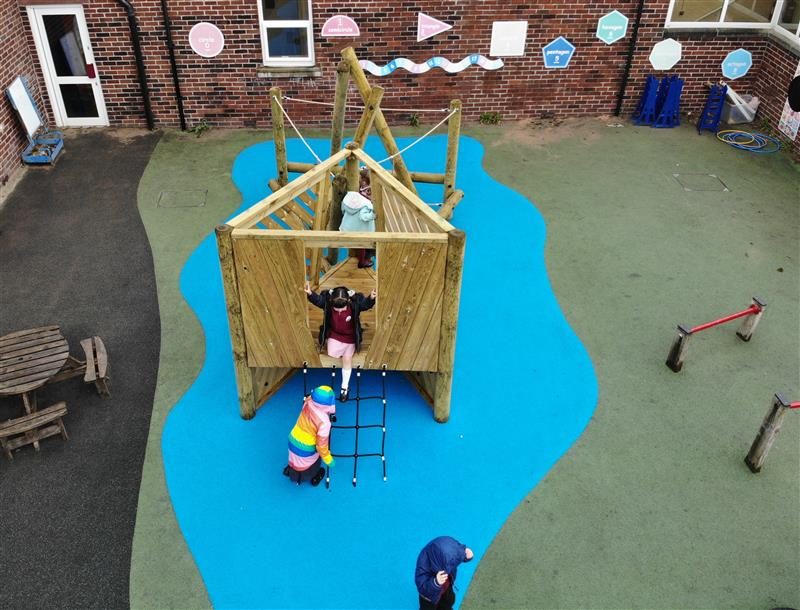 3 children, one wearing a multi-coloured raincoat are playing on a climbing frame that has been installed onto blue wetpour surfacing in front of the school building.