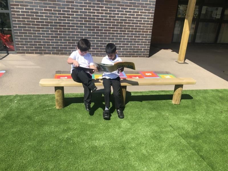 2 children wearing white polo t-shirts and black trousers sat on a bench reading books, the bench has been installed onto artificial grass in front of the school building.