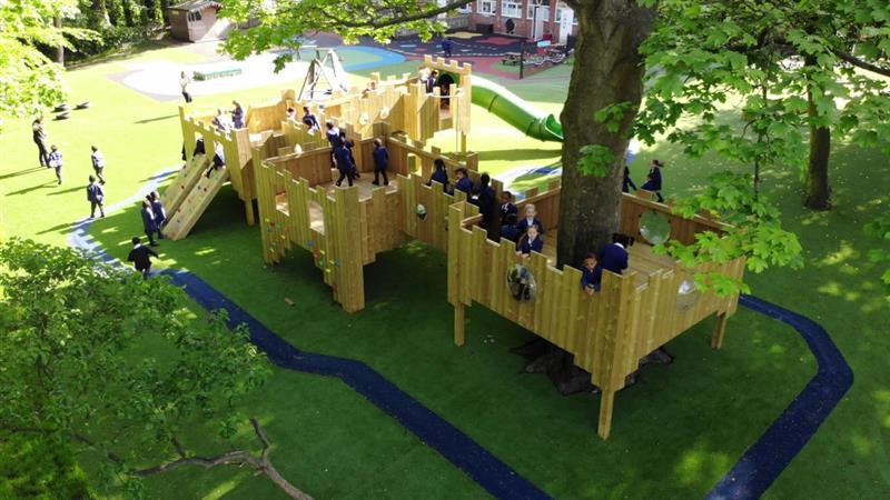Lots of children wearing blue school jumpers playing inside a bespoke treehouse that has been built around a very large tree with a big green slide attached to the treehouse.