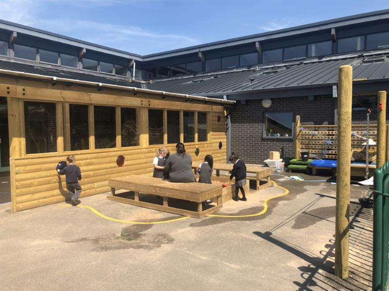 3 children playing in a large sandbox that has been installed onto the school playground whilst one teacher wearing a grey top sits on the side of the sandbox. There is a large outdoor classroom behind the sandbox where one child is walking past and touching a blue circle.