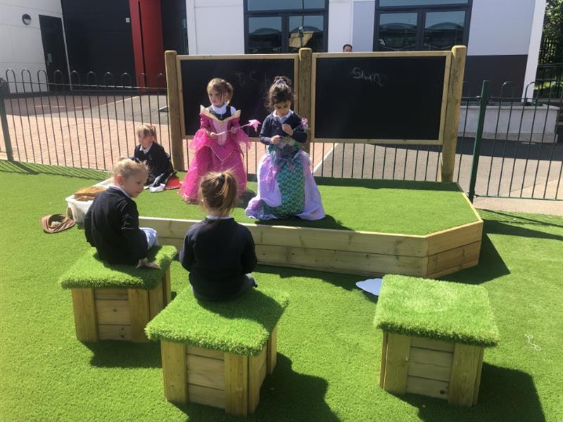 Children performing on a playground performance stage