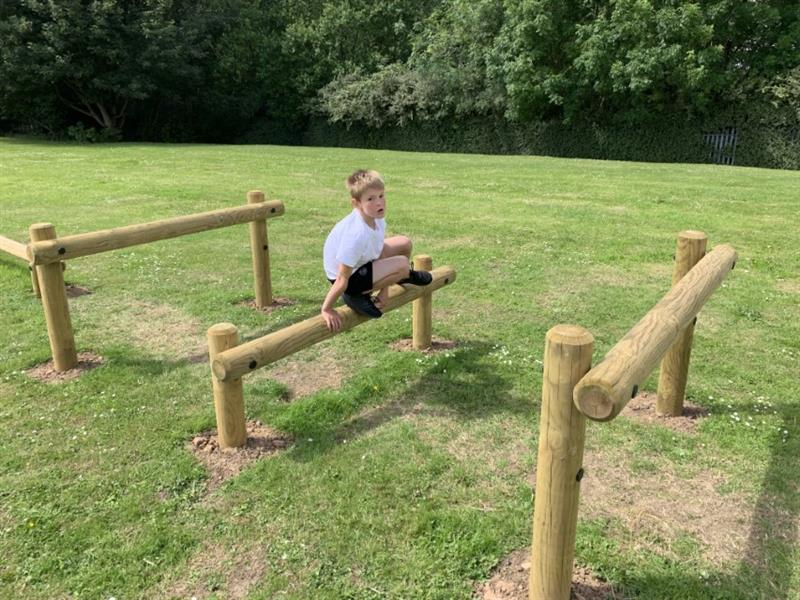 One boy wearing a white polo top is jumper over timber posts as part of an obstacle course. The timber posts have been installed into the grass.