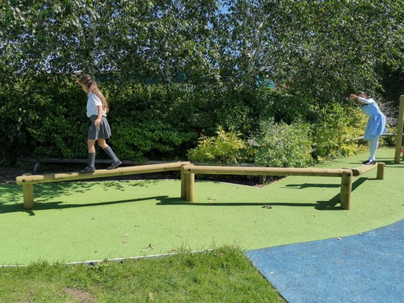 Two girls, one wearing a summer dress and one wearing a grey skirt and white top are playing on a trim trail that has been installed onto wetpour surfacing in front of a row of trees.