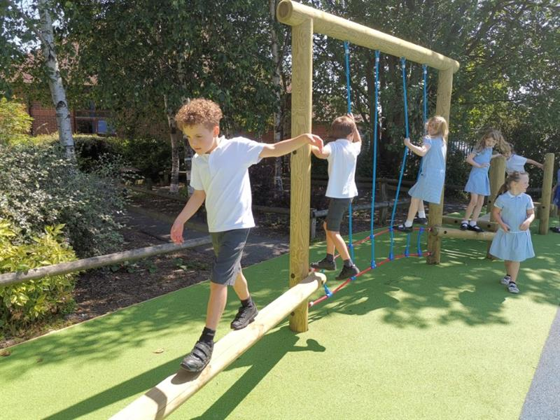 6 children, 2 boys and 3 girls playing on a trim trail in the sunshine which has been installed onto wet pour surfacing.