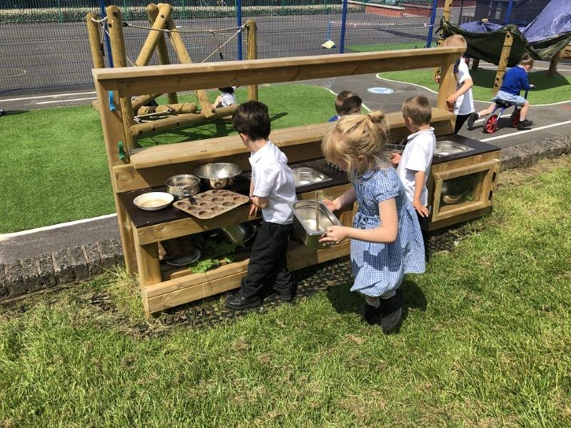 3 children playing at a mud kitchen, one girl wearing a blue summer dress and two boys wearing white shirts whilst other children play in the background.
