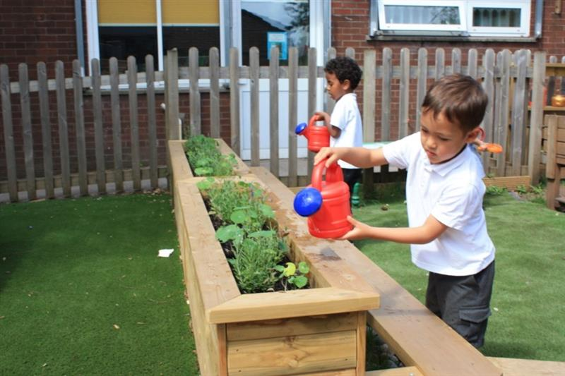 Child watering plants in a playground planter
